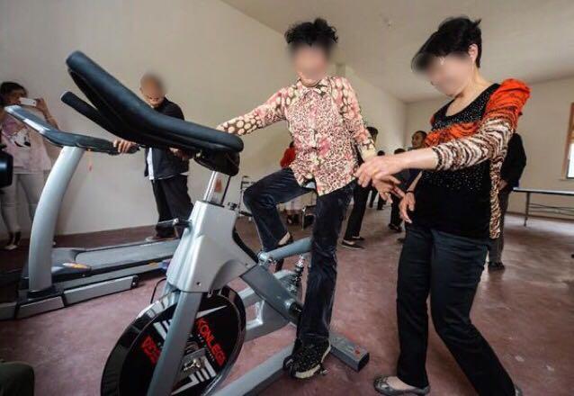 トレーニングマシンにまたがり会話を楽しむ初老の女性